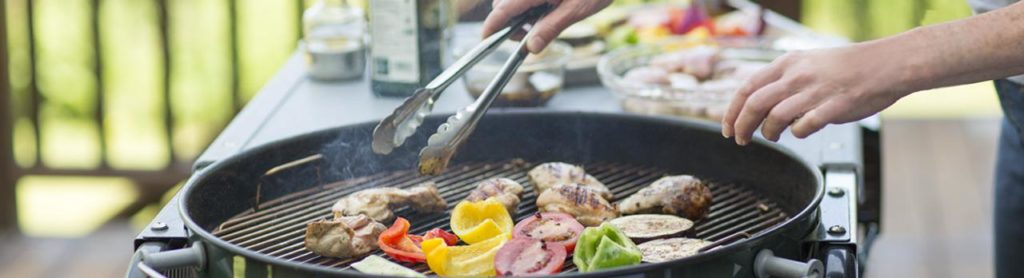 Person grilling chicken and vegetables.