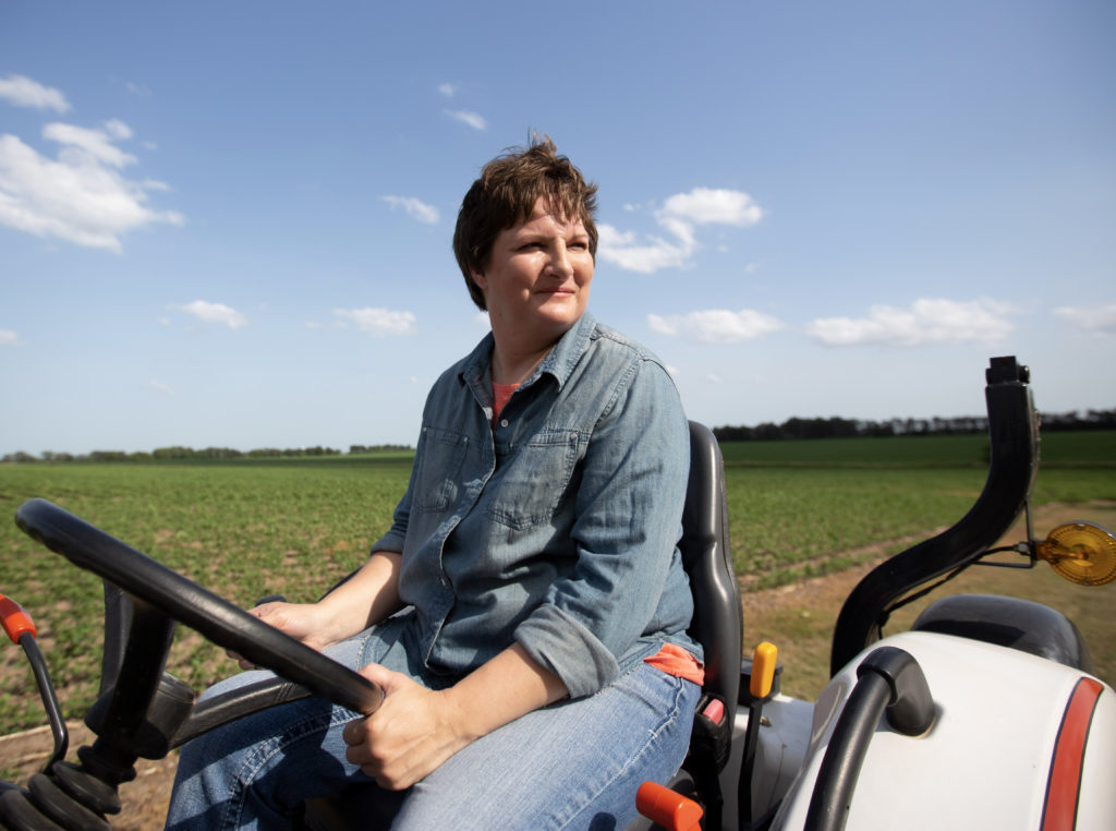 Farmer driving around her field in an ATV